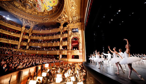 Dancers on stage with audience and orchestra